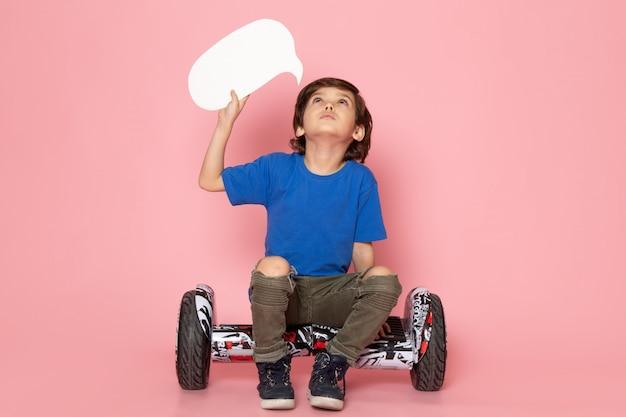 Ein süßer junge der vorderansicht im blauen t-shirt, der auf dem segway auf dem rosa raum sitzt