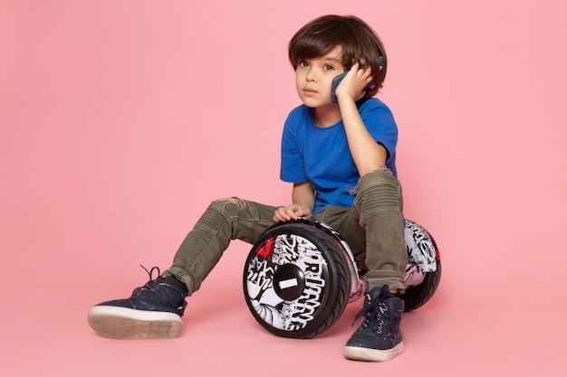 Ein süßer junge der vorderansicht im blauen t-shirt und in der khakihose, die am telefon sprechen segway auf dem rosa boden reiten