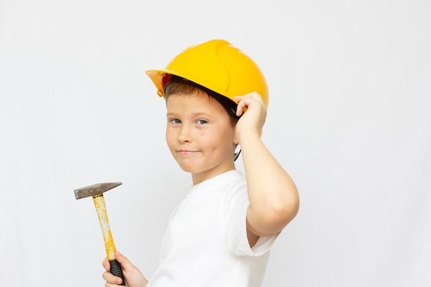 Ein süßer junge in einem schutzhelm, in den händen eines kindes mit einem hammer. das konzept der bedeutung der verwendung von persönlicher schutzausrüstung und spezialwerkzeugen