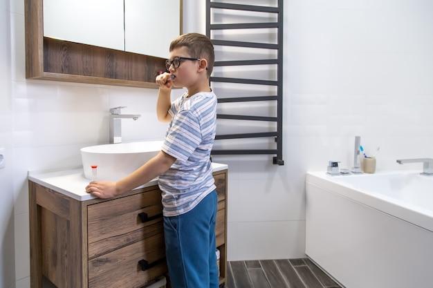 Ein süßer kleiner junge, der seine zähne putzt und die stunde mit einer sanduhr bestimmt.