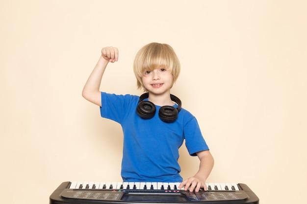 Ein süßer kleiner junge der vorderansicht, der im blauen t-shirt mit schwarzen kopfhörern lächelt, die kleines niedliches klavier spielen