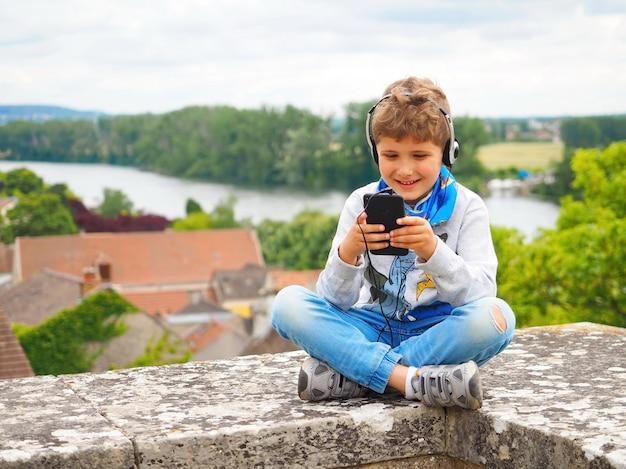 Ein süßer kleiner junge hört musik mit kopfhörern. er mag musik. es gibt einen fluss und dächer von häusern