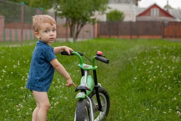 Ein süßer kleiner junge mit einem fahrrad in der nähe des hauses, ein sport für kinder, eine aktive familie auf der straße.