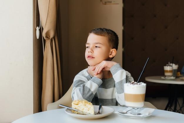 Ein süßer kleiner junge sitzt in einem café und betrachtet eine nahaufnahme von kuchen und kakao. diät und richtige ernährung.