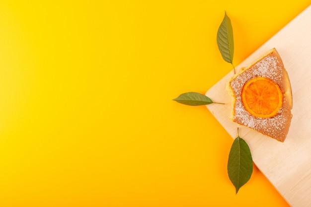 Ein süßer köstlicher leckerer orangenkuchen des draufsichts auf dem cremefarbenen holzschreibtisch und dem süßen zuckerkeks des gelben hintergrunds