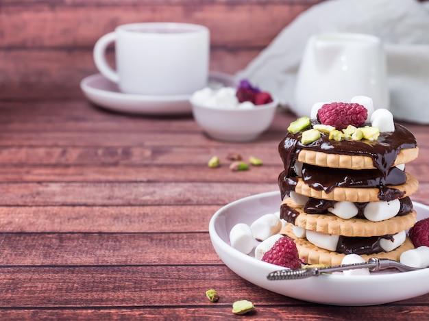 Ein süßer nachtisch des schokoladenkekses, des himbeeribischs und des tasse kaffees auf dunklem hintergrund
