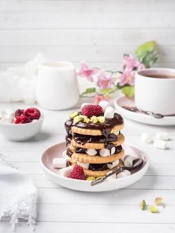 Ein süßer nachtisch einer schokoladenplätzchenhimbeere und des eibischbechers tasse kaffee auf einer leuchttabelle