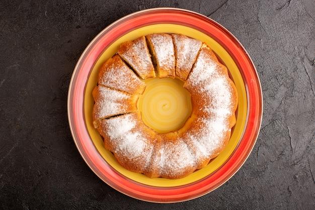 Ein süßer runder kuchen der draufsicht mit geschnittenem süßem köstlichem lokalisiertem kuchen des zuckerpulvers in teller und grauem hintergrundkekszuckerplätzchen