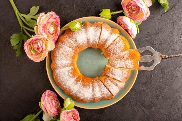 Ein süßer runder kuchen der draufsicht mit zuckerpulver auf der oberseite geschnittenen süßen köstlichen isolierten innenplatte zusammen mit blumen und grauem hintergrundkekszuckerkeks
