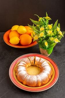 Ein süßer runder kuchen der draufsicht mit zuckerpulver geschnitten süßer köstlicher isolierter kuchen innerhalb platte zusammen mit zitronen und grauem hintergrundkekszuckerplätzchen