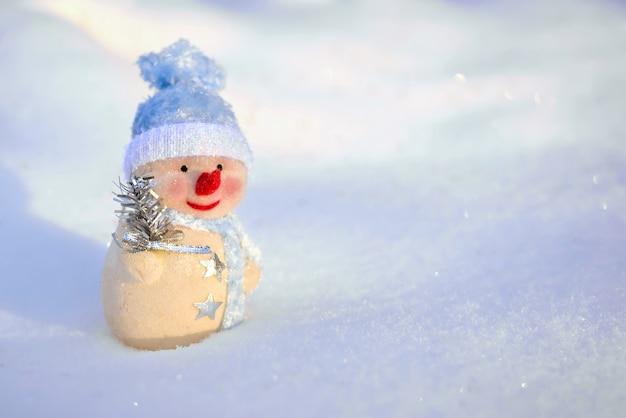 Ein süßer spielzeugschneemann in einer blauen mütze auf dem schnee im winter