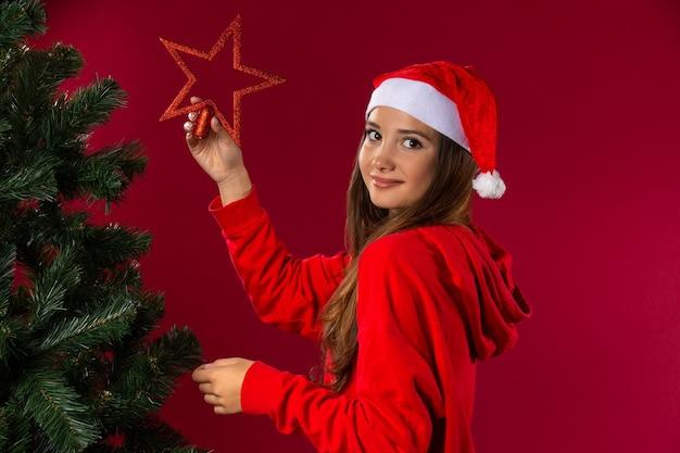 Ein süßes, angenehmes mädchen in einer weihnachtsmannmütze schmückt einen weihnachtsbaum und freut sich auf schöne feiertage mit einem lächeln.
