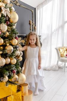 Ein süßes blondes mädchen schmückt vor weihnachten zu hause einen baum. glückliche kindheit. einen weihnachtsbaum vor weihnachten schmücken.