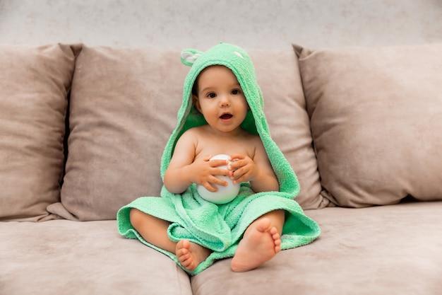 Ein süßes kind, das in ein handtuch gewickelt ist, sitzt auf dem bett. baby in einem badetuch.