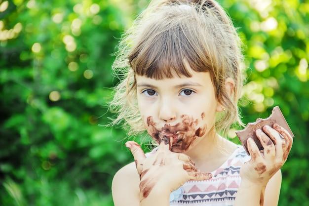 Ein süßes kind isst schokolade. selektiver fokus