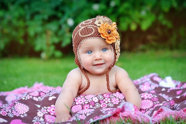 Ein süßes kleines baby schaut in die kamera und trägt einen braunen hut