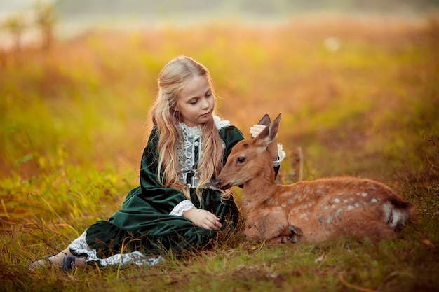 Ein süßes kleines blondes mädchen in einem grünen vintage-kleid sitzt neben einem kleinen sikahirsch um sie herum gelbe schöne herbstbäume.