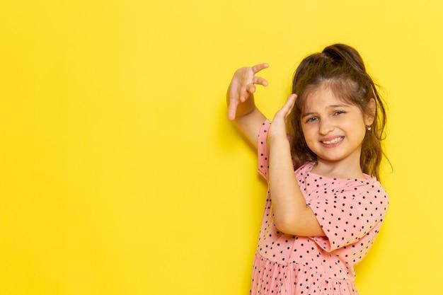 Ein süßes kleines kind der vorderansicht im rosa kleid bedeckt ihr gesicht