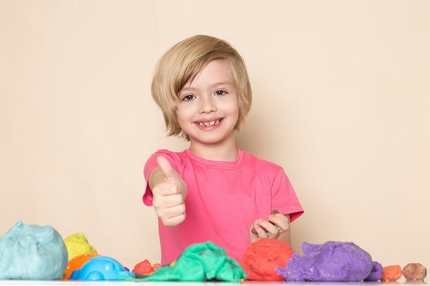 Ein süßes kleines kind der vorderansicht im rosa t-shirt, das fantastisches zeichen zeigt, das mit buntem kinetischem sand spielt