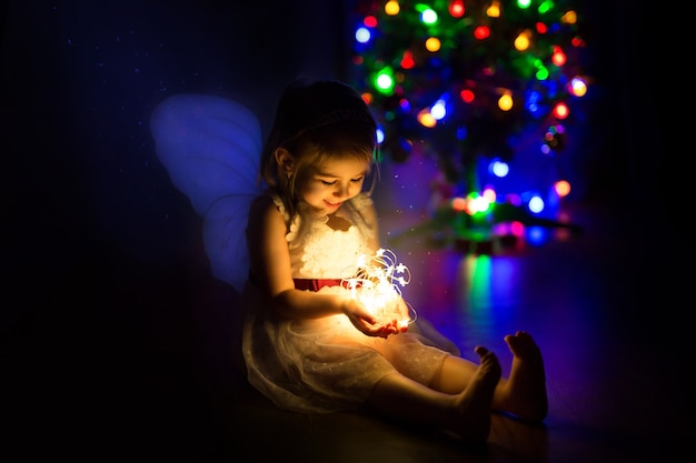 Ein süßes kleines mädchen beleuchtet eine weihnachtsgirlande einen magischen feiertag