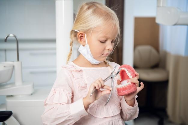 Ein süßes kleines mädchen, das mit einem künstlichen kiefer und medizinischen instrumenten in einer zahnklinik spielt