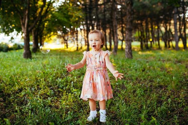 Ein süßes kleines mädchen, das mit seifenblasen im park spielt.