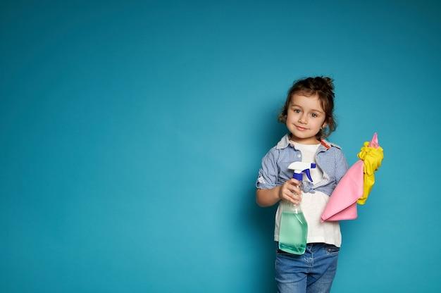 Ein süßes kleines mädchen hält einen lappen, um den staub abzuwischen und mit reinigungsmittel in den händen zu sprühen