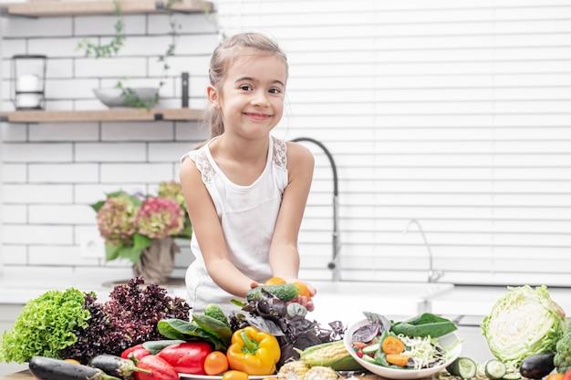 Ein süßes kleines mädchen hält frisches gemüse, während es einen salatkopierraum vorbereitet. Premium Fotos