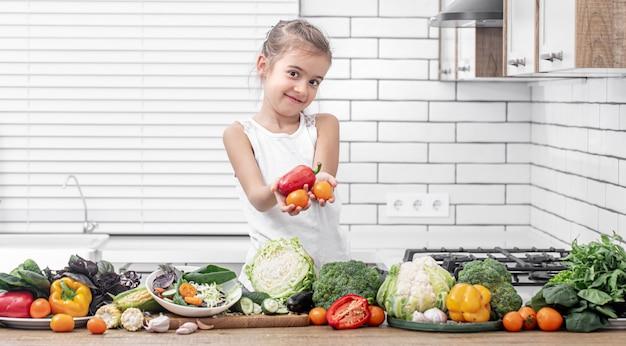 Ein süßes kleines mädchen hält frisches gemüse, während es einen salatkopierraum vorbereitet.