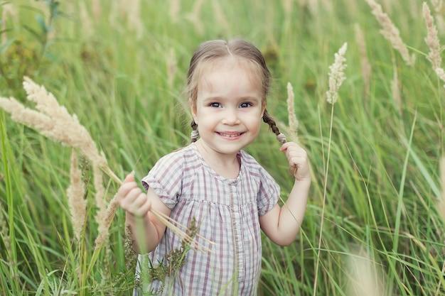 Ein süßes kleines mädchen in einem kleid auf einem weizenfeld mit ährchen im sommer, das einen strauß ährchen in den händen hält, schaut in die kamera und lächelt und hält ihren zopf mit der hand. natur