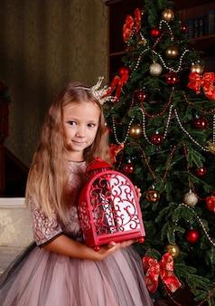 Ein süßes kleines mädchen in einem kleid, das sich auf neujahr vorbereitet. in erwartung der partei,