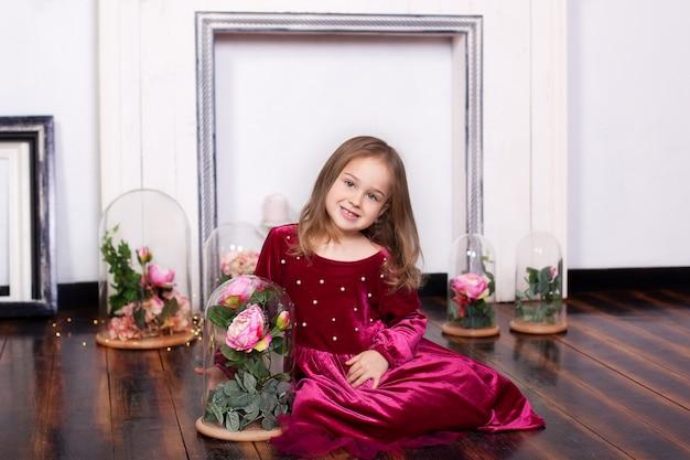 Ein süßes kleines mädchen in einem kleid sitzt auf dem boden mit blumen rose in einer flasche. kamera betrachten. kleine prinzessin. konzept einer glücklichen kindheit. porträt des glücklichen gesichtskindes. geburtstag, feiertag, geschenk