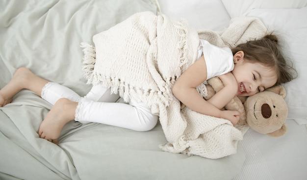 Ein süßes kleines mädchen schläft in einem bett mit einem teddybärspielzeug.