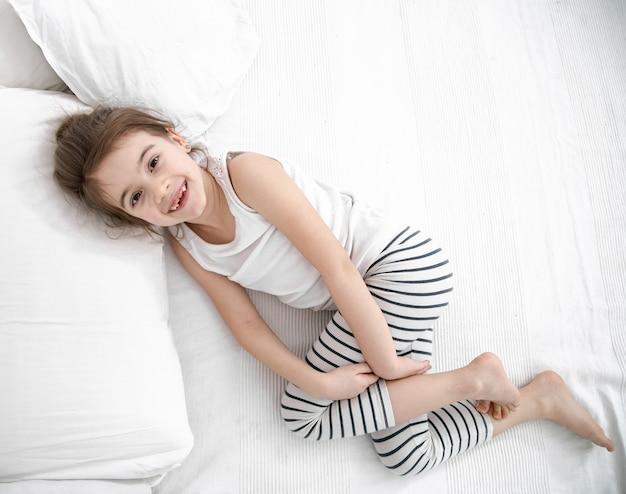 Ein süßes kleines mädchen schläft in einem weißen bett. konzept der kindlichen entwicklung und des schlafes.