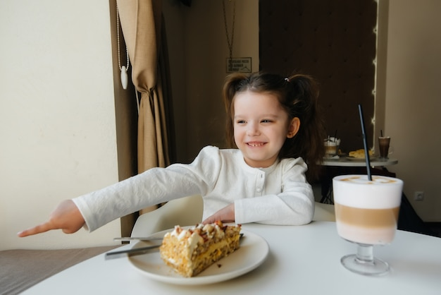 Ein süßes kleines mädchen sitzt in einem café und betrachtet eine nahaufnahme von kuchen und kakao. diät und richtige ernährung.