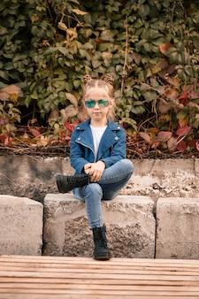 Ein süßes kleines mädchen sitzt mit sonnenbrille auf einem steinzaun. stilvolles kind in einer blauen jacke. lässiger stil, mode für kinder, modischer anzug, glückliche kindheit