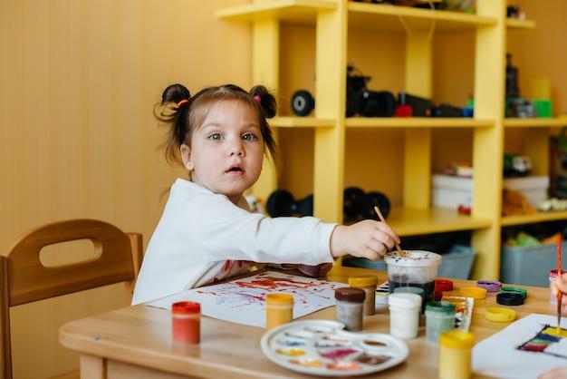 Ein süßes kleines mädchen spielt und malt in ihrem zimmer. erholung und unterhaltung.