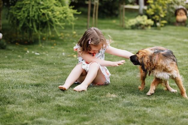Ein süßes kleines mädchen spielt zu hause mit ihrem hund auf gras auf gras