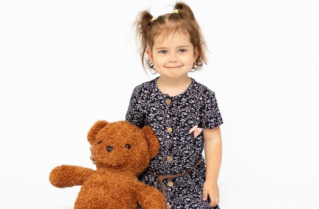 Ein süßes kleines mädchen umarmt einen teddybären