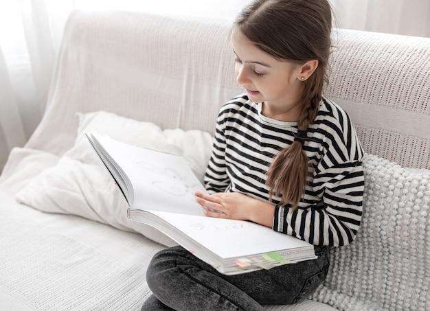Ein süßes kleines mädchen untersucht begeistert ein buch und sitzt zu hause auf der couch