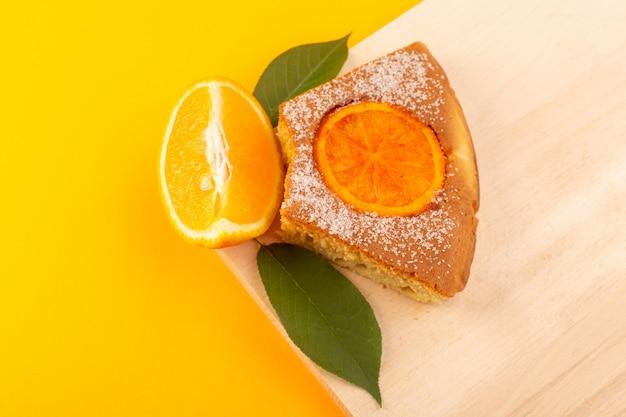 Ein süßes leckeres leckeres stück des orangenkuchenstücks der draufsicht auf dem cremefarbenen holzschreibtisch und dem süßen zuckerkeks des gelben hintergrunds