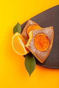 Ein süßes leckeres leckeres stück orangenkuchenscheibe von oben, auf dem braunen holzschreibtisch und dem süßen zuckerkeks des gelben hintergrunds