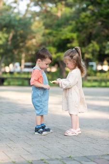 Ein süßes lockiges mädchen hilft beim auspacken einer süßigkeit und behandelt einen jungen, der vorne in der mitte eines baumes steht