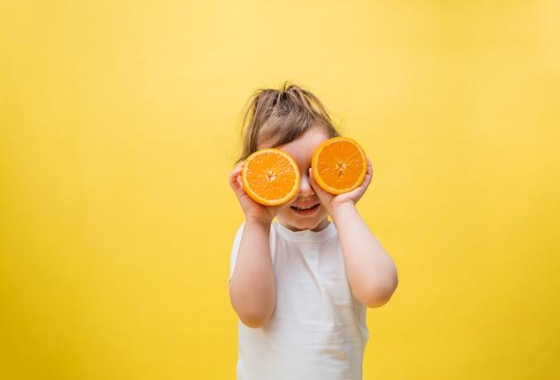 Ein süßes mädchen hält halbe orangen vor die augen. ein kleines mädchen in einem weißen t-shirt auf einem gelben raum.