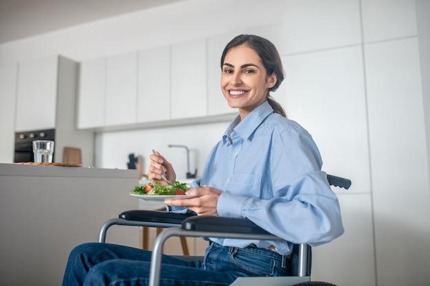 Ein süßes mädchen im rollstuhl in der küche zu hause