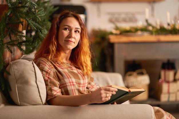 Ein süßes mädchen liest ein buch in einer warmen und gemütlichen atmosphäre. entspannungs- und datenschutzkonzept.