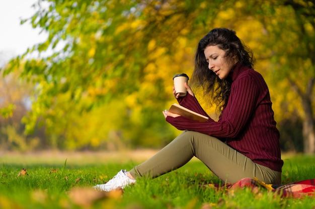 Ein süßes mädchen liest ein buch und trinkt kaffee auf einem grünen rasen in einem herbstpark. herbststimmung. ein gemütlicher ort, um mit sich allein zu sein.