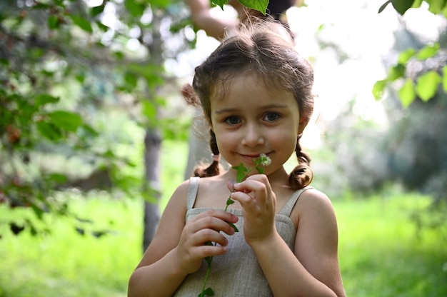 Ein süßes mädchen posiert schüchtern vor der kamera mit einer wildblume in den händen in der nähe ihres gesichts vor dem hintergrund ihrer mutter, die an einem sommertag in den strahlen des sonnenuntergangs im garten kirschen pflückt