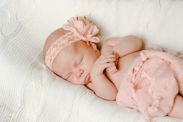 Ein süßes neugeborenes mädchen, eingewickelt in eine zarte rosa decke mit einem rosa verband, schläft auf einer weißen strickdecke,