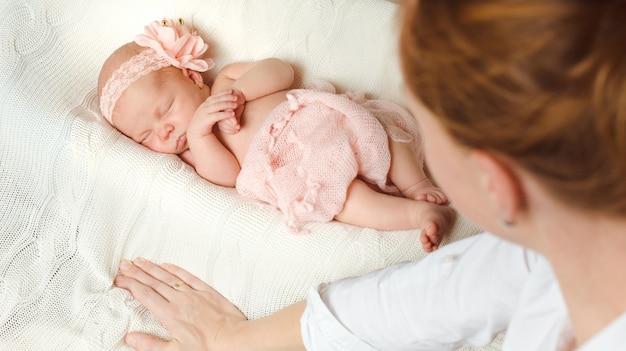 Ein süßes neugeborenes mädchen schläft auf einer weißen strickdecke und faltet die hände.